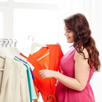 clothing, fashion, style and people concept - happy plus size woman choosing clothes at home wardrobe