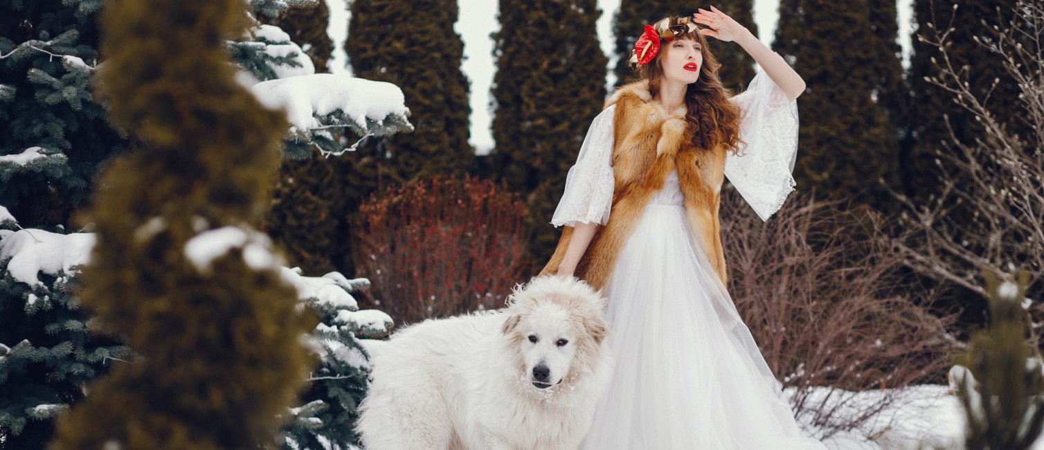 Woman in a winter forest. Lady with dog. Girl in a long white dress