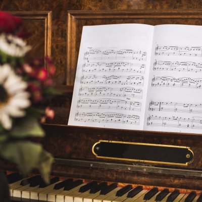 Opened Music Book on Beautiful Old Piano with Flowers in Foreground