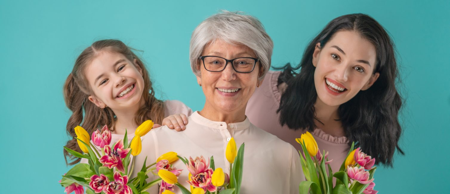 Happy women's day! Child daughter is congratulating mom and grandma giving them yellow flowers tulips.Granny, mum and girl smiling and hugging on light blue background. Family holiday and togetherness.