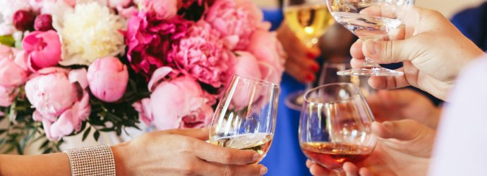 Guests clang glasses of champagne and whisky before a pink bouquet