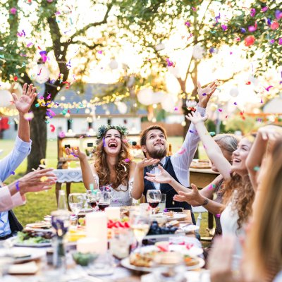 Wedding reception outside in the backyard. Bride and groom with family and guests sitting around the table, having fun.
