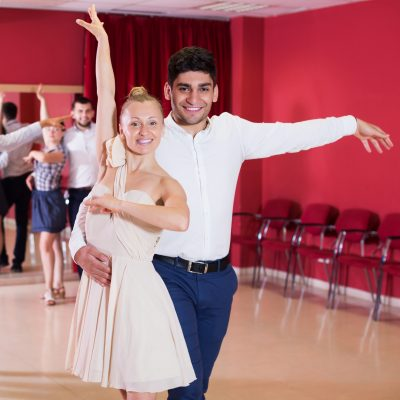Happy adult couples enjoying latin dances in modern studio