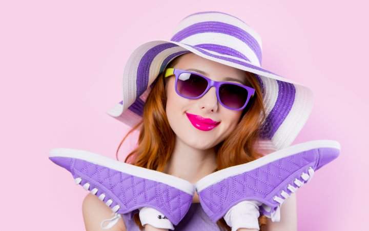 Young redhead girl in sunglasses and hat holding shoes on pink background