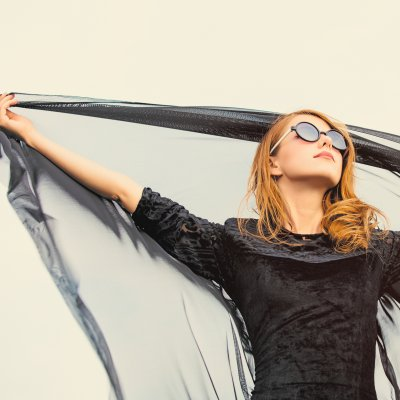 photo of beautiful young woman holding shawl on the wonderful  sky background