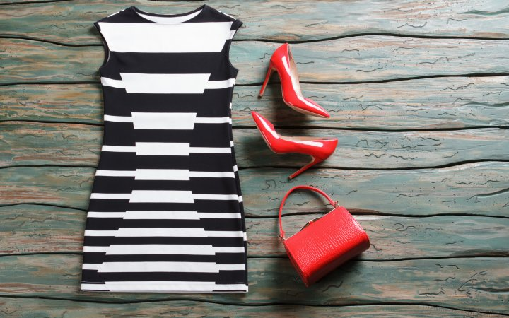 Sleeveless dress and heel shoes. Bright red purse and heels. Attractive evening outfit for summer. Woman's clothing on auction.