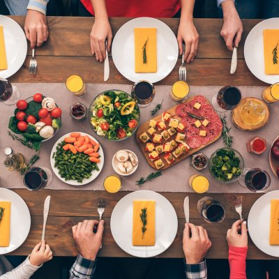 Family is sitting at the table and does not eat. Festive table set for six people. Wooden background top view mock-up