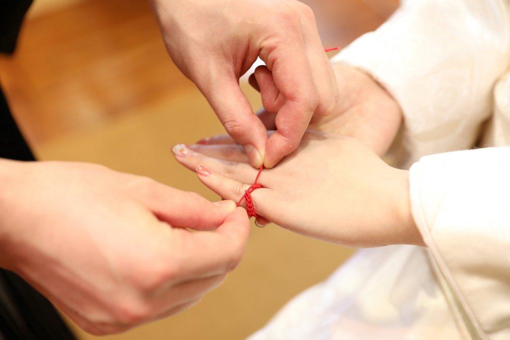 お互いの左手小指に結び付ける「結い紐」の儀