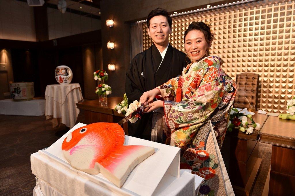 ケーキの代わりに鯛をかたどったかまぼこに入刀するカップル